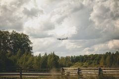 The plane flies over the forest. Clouds in the sky royalty free stock image