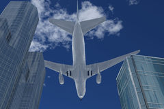Plane flies over high-altitude buildings Royalty Free Stock Photos