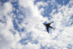 The plane flies in the sky against the background of clouds Royalty Free Stock Photos