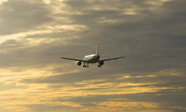 The plane flies at sunset in a cloudy sky Stock Photography