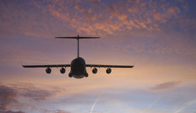 Plane Flies Towards Sunset. Military transport plane towards the brilliant sunset Royalty Free Stock Photos