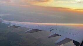 The plane flies and turns aligns at sunset