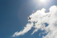 Plane in flight. Pictured on the plane in flight against the blue sky and bright sun Stock Images