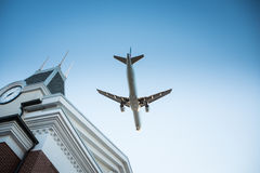 Plane Flyby. Plane flying by over a building with a clock Royalty Free Stock Image
