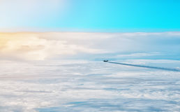 Plane flying above the clouds in the early morning. Royalty Free Stock Image
