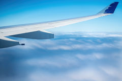 Plane flying above clouds Stock Photo