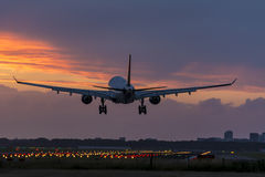 Plane is flying above the runway. Stock Images