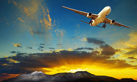 Plane flying against beautiful sun rising sky for traveling them. E Royalty Free Stock Image