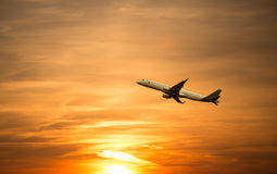 A plane flying at beautiful sunset Royalty Free Stock Images