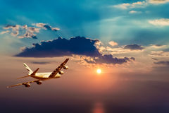 A plane flying in a beautiful sunset. A plane flying towards a beautiful sunset Royalty Free Stock Photos