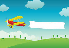 Plane flying with blank banner. Colorful illustration of retro biplane flying over countryside trailing blank banner or message board Royalty Free Stock Images