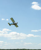 Plane flying in the clouds over the field Royalty Free Stock Images
