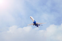 Plane flying through clouds in the sky. Jet aircraft. Stock Image
