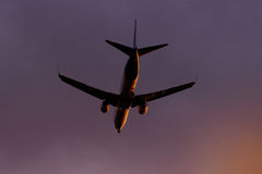 Plane flying through clouds towards sunset in the sky. Jet aircraft. Royalty Free Stock Image