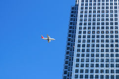Plane flying dangerously close to a building. Plane flying close to a skyscraper with hundreds of windows Stock Photo