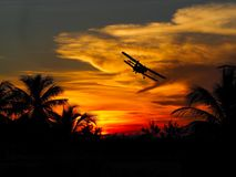Plane flying into off the sunset. Plane flying high into the clouds at sunset royalty free stock photo