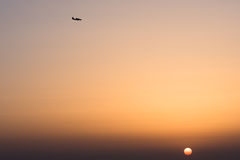 Plane flying high in the sky above the setting sun Royalty Free Stock Photo