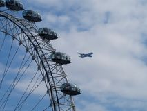 A plane flying and the London Eye Royalty Free Stock Photos