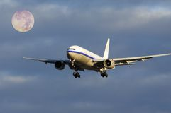 Plane flying with moon. Plane flying with early full moon Royalty Free Stock Image