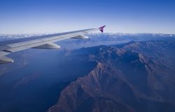 Plane flying in mountain. Jet plane wing and Italy Alps view Royalty Free Stock Image