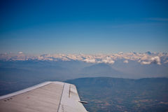 Plane flying next to the french alps. Plane wing tip flying over french alps and mont blanc Royalty Free Stock Photography