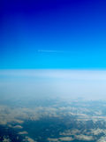 Plane flying over Alps. Aeroplane flying through clear blue sky over the Swiss Alps with vapour trail Stock Photo