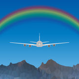 Plane flying over blue sky with rainbow over high mountains Stock Images