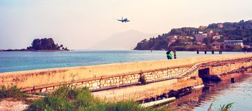 The plane is flying over a bridge across the sea to the airport. Of Corfu, Greece royalty free stock image