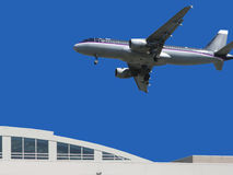 Plane flying over building. A plane flying in the blue sky over a building Royalty Free Stock Photo