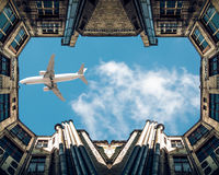 Plane flying over buildings stock photography