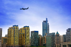 Plane flying over city Stock Images
