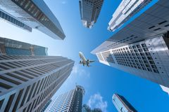 Plane flying over city on blue sky Stock Photos