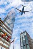Plane flying over the city Stock Photography