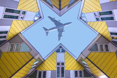 Plane flying over the cubic houses at Rotterdam. Plane flying over the modern Yellow cubic houses in Rotterdam, Netherlands Stock Photography