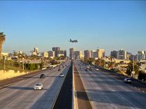 Plane flying over freeway with city skyline in the background Royalty Free Stock Photo