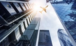 Plane over highrise buildings. Plane flying over highrise office buildings in the sun, financial district London, Great Britain Royalty Free Stock Images