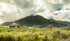 Plane flying over huts in remote tropical location. Small plane flying over huts in remote tropical location stock image