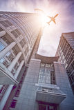 Plane flying over modern office skyscraper Stock Photo