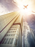 Plane flying over modern office skyscrapers stock images