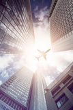 Plane flying over modern office skyscrapers Royalty Free Stock Photo