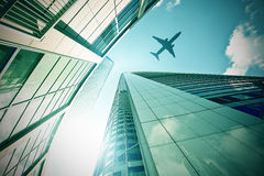 Plane flying over modern office towers Royalty Free Stock Image