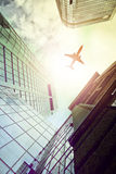 Plane flying over modern office towers Royalty Free Stock Photos
