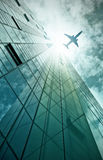 Plane flying over office building Stock Photos