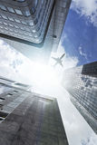 Plane flying over office towers Royalty Free Stock Photo