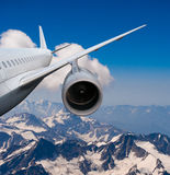 Plane flying over the snow-capped mountains. Airplane flying down. against the sky.  landing or crash of airplane. no people, no bodies Stock Photo