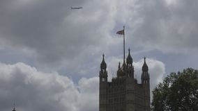 The plane is flying over the tower. Flag of Britain. stock footage