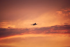 Plane flying upon red sky Stock Photos