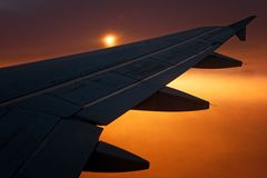 Plane flying silhouette wing at sunset sunrise. Plane flying silhouette wing at sunset or sunrise stock photo