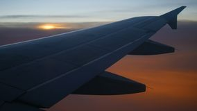 Plane flying silhouette wing at sunset sunrise. Plane flying silhouette wing at sunset or sunrise stock footage
