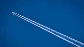 Plane flying in the sky. The plane is flying against the blue sky. The plane has a vapor trail Stock Image